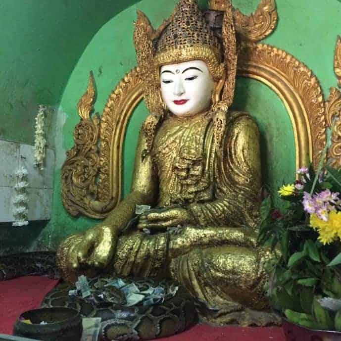 buddha statue with snakes in snake pagoda mandalay myanmar