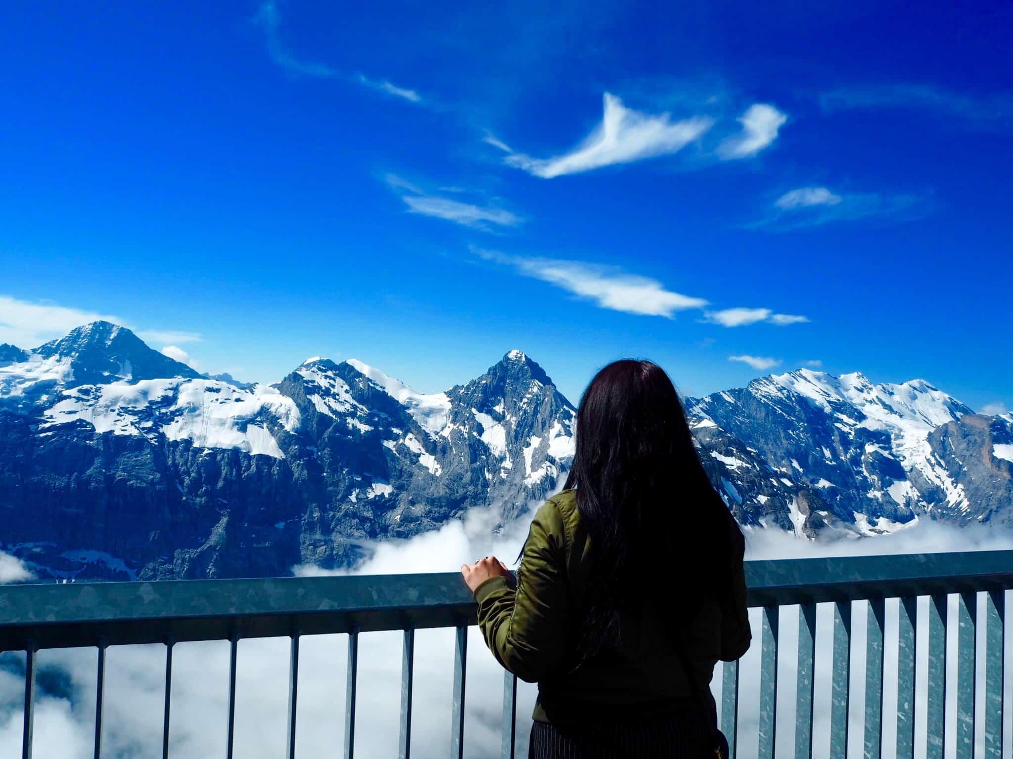 Girl overlooking the mountain view of Schilthorn Piz Gloria James Bond film location