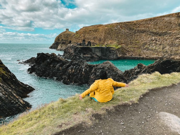 Girl in Yellow coat looking out at the Blue Lagoon in Pembrokeshire Wales