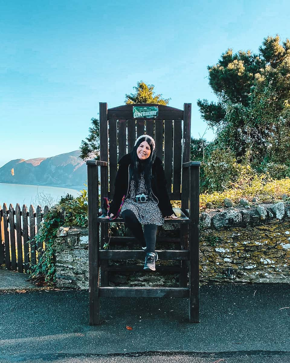 Girl sitting on giant chair on the Lynton and Lynmouth Cliff Railway Upper Station