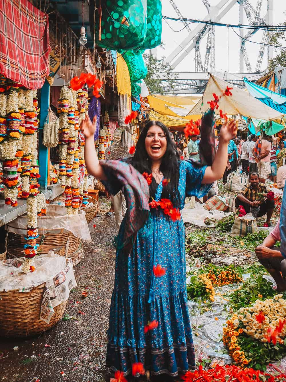 English girl throwing flowers at Mallick Ghat Flower Market