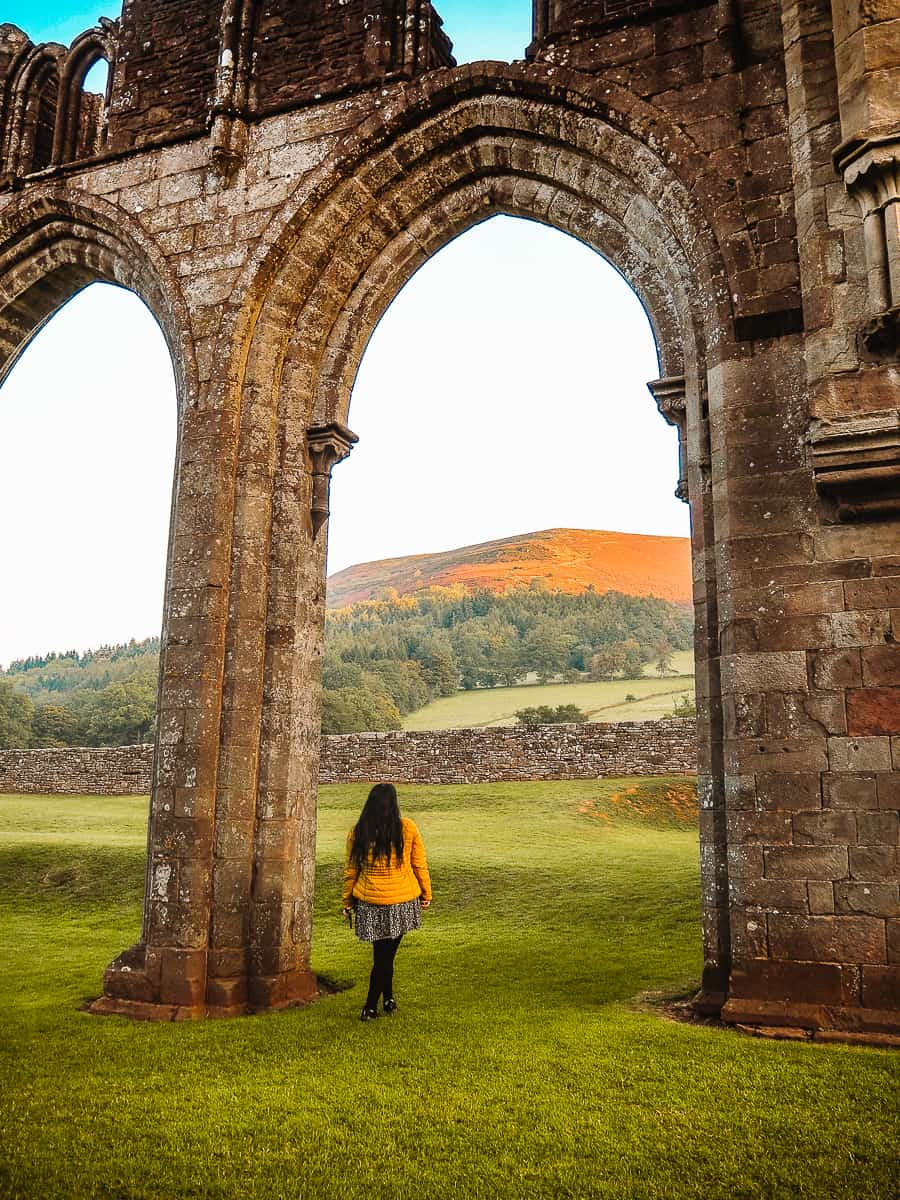 Exploring Llanthony Priory Ruins with a backdrop of the Black Mountains in Brecon Beacons National Park