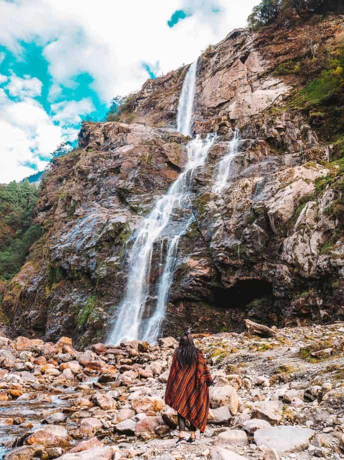 Girl standing below Nuranang Falls Arunachal Pradesh Bong Bong Falls