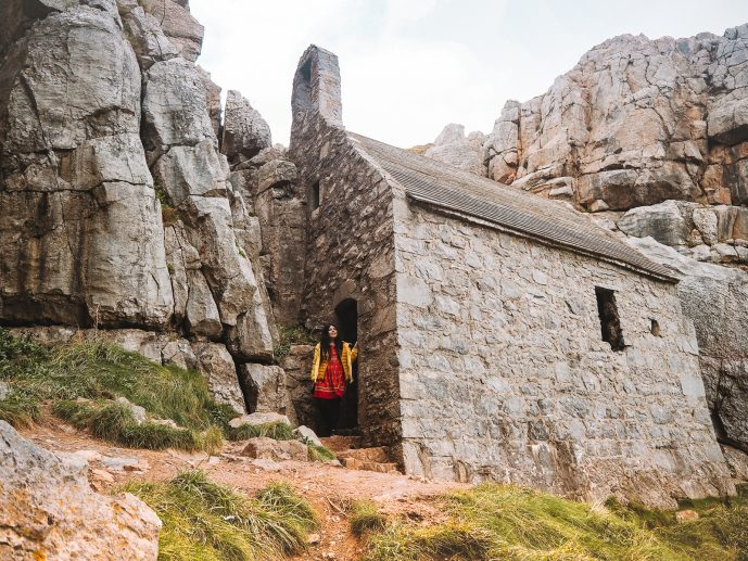 Girl visiting St Govan's Chapel in Pembrokeshire Wales